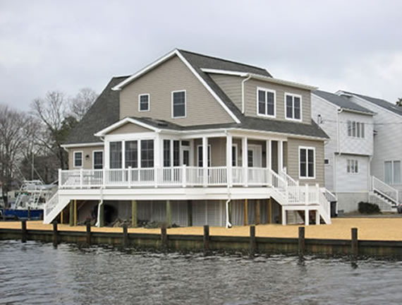 Custom designed cape style modular home takes advantage of lagoon water view from its deck and sun room on side of house.