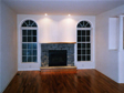 All stone fireplace surround with raised hearth looks beautiful between the specialty circle top windows